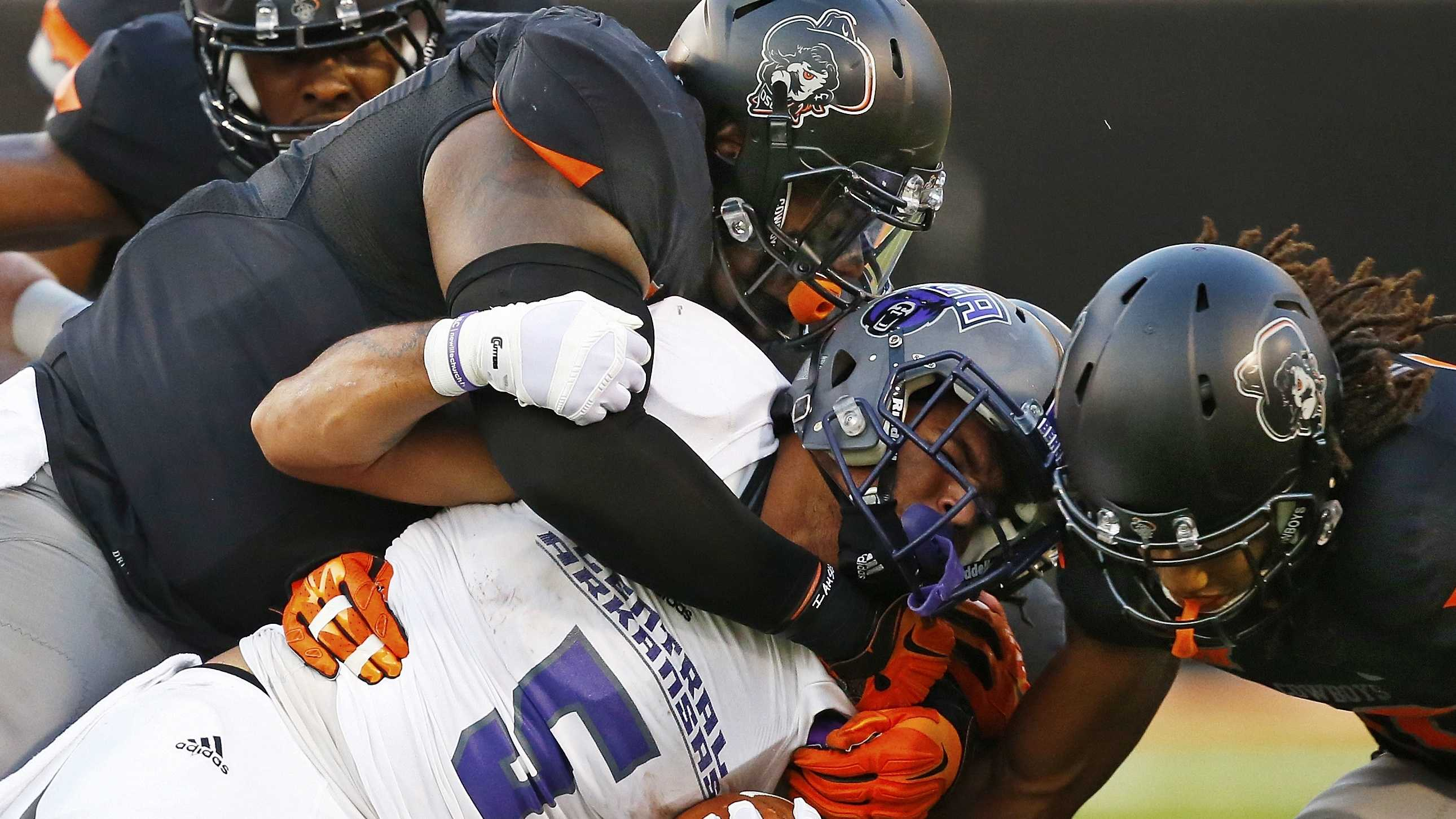 Central Arkansas running back Dominique Thomas (5) is tackled by a number of Oklahoma State defenders in the first quarter of an NCAA college football game in Stillwater, Okla., Saturday, Sept. 12, 2015. (AP Photo/Sue Ogrocki)