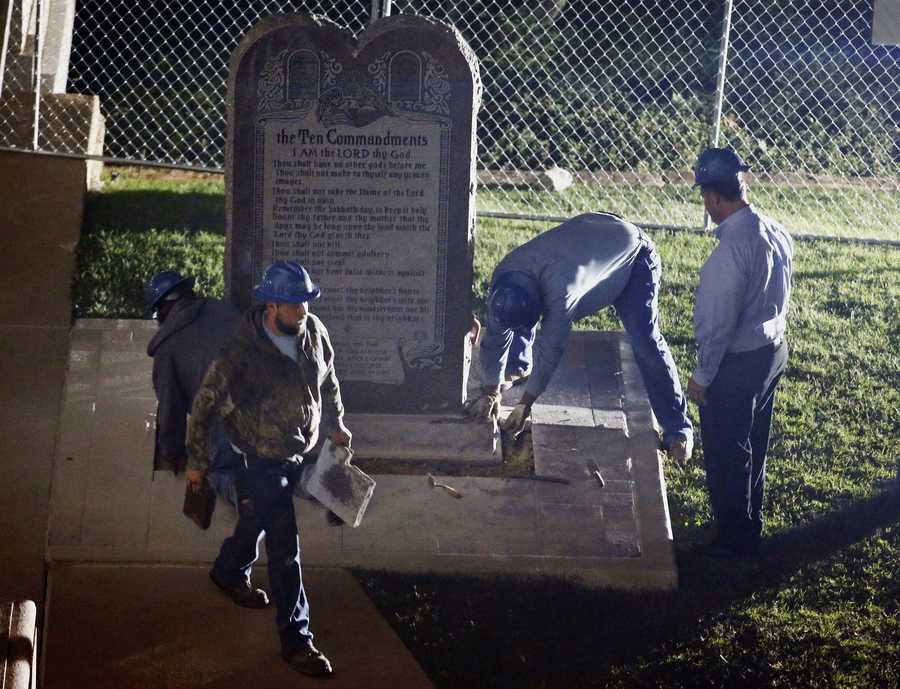 "Workers remove the controversial Ten Commandments monument from the grounds of the state Capitol in Oklahoma City, late Monday, Oct. 5, 2015. The removal comes after the Oklahoma Supreme Court's decision in June that the display violates a state constitutional prohibition on the use of public property to support ""any sect, church, denomination or system of religion."" (AP Photo/Sue Ogrocki)"