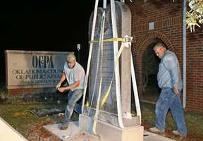 "Workers place the Ten Commandments monument in its new home at the Oklahoma Council of Public Affairs, just down the street from the state Capitol, in Oklahoma City, early Tuesday, Oct. 6, 2015. The monument was removed from the state Capitol late Monday after the Oklahoma Supreme Court's decision in June that the display violates a state constitutional prohibition on the use of public property to support ""any sect, church, denomination or system of religion."" (AP Photo/Sue Ogrocki)"