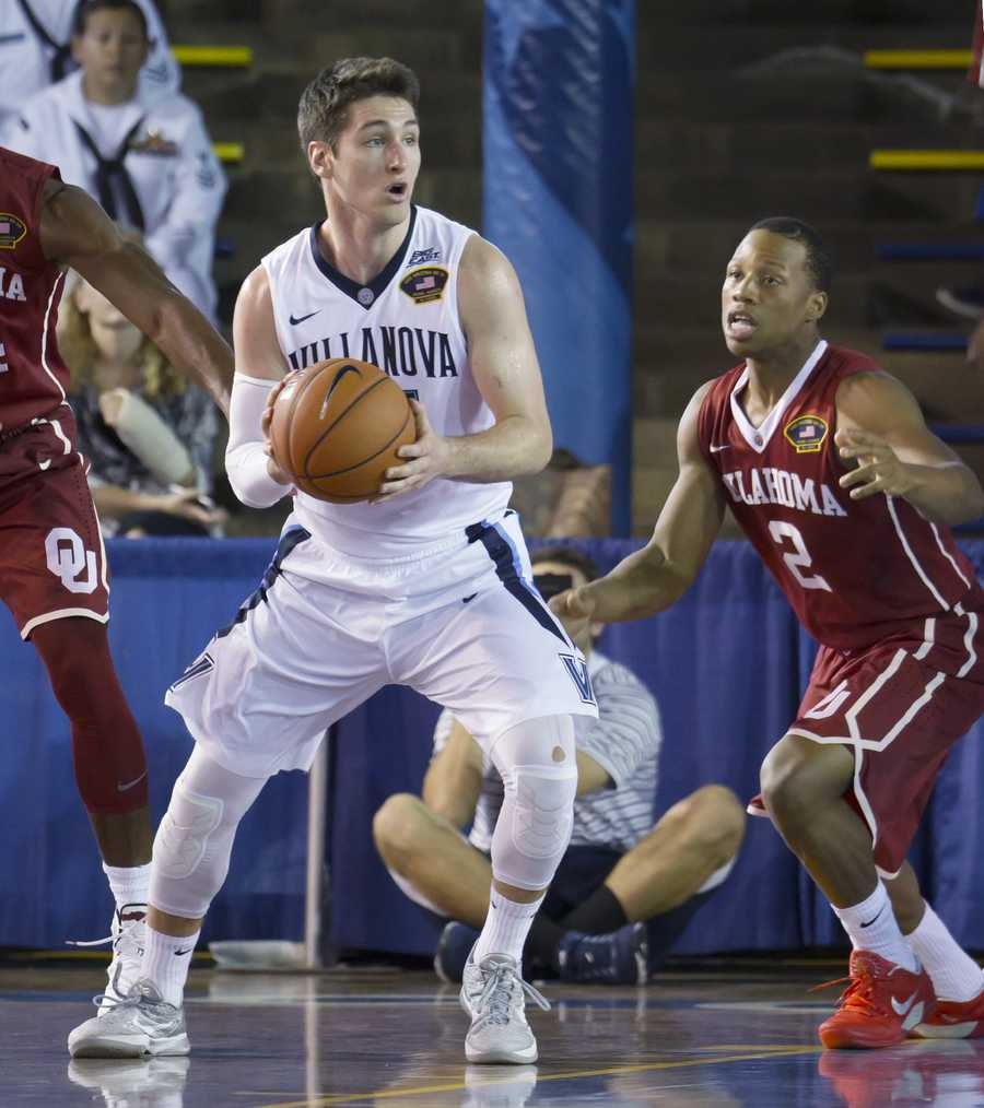 Villanova guard Ryan Arcidiacono, left, looks for an open teammate to pass to while being guarded by Oklahoma guard Dinjiyl Walker (2) in the first half of an NCAA college basketball game at the Pearl Harbor Invitational on Monday, Dec. 7, 2015, in Honolulu.