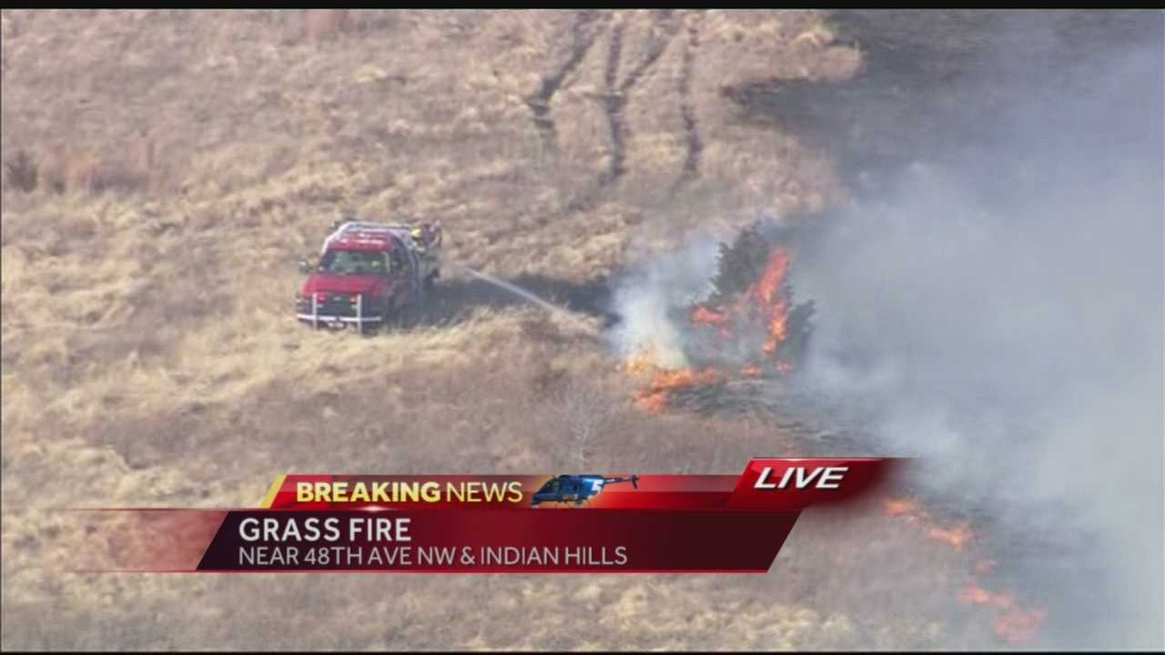 Fire crews continue to battle a grass fire in northwest Norman Thursday afternoon.