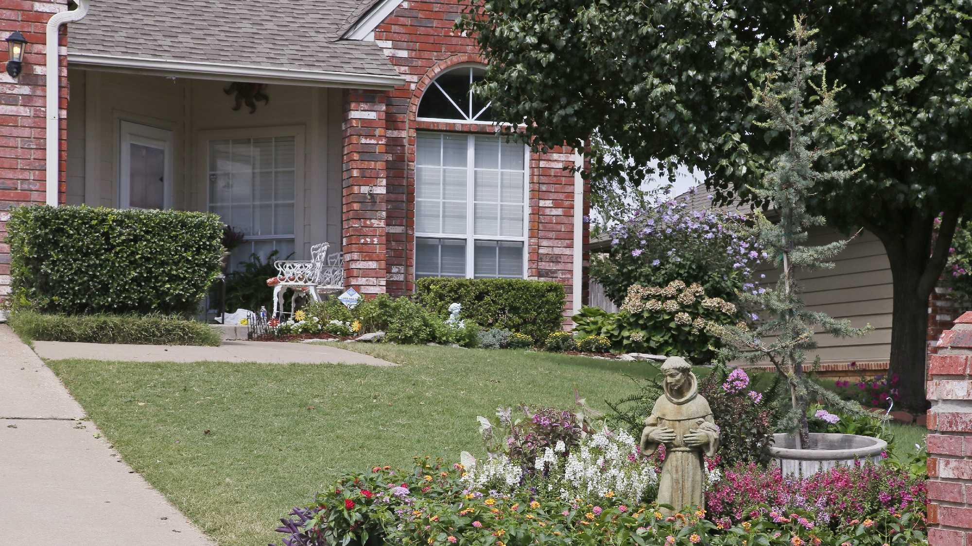 Flowers and a statue of St. Francis in a memorial display are pictured on the front lawn of the Jabara family in Tulsa, Okla., Friday, Aug. 19, 2016. Khalid Jabara was allegedly shot and killed outside his home by neighbor Stanley Majors on Aug. 12, 2016. (AP Photo/Sue Ogrocki)