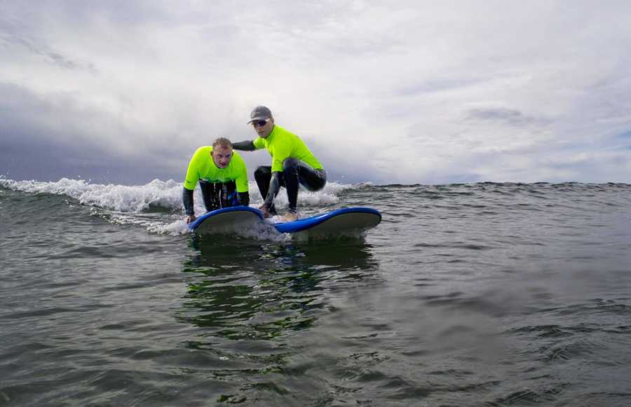 Professional surfers dive into the ocean off Cowell Beach and teach soldiers how to surf one-on-one.