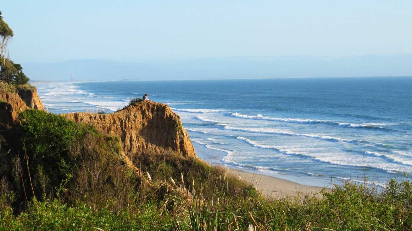 A young couple watches the waves from cliffs in Aptos.