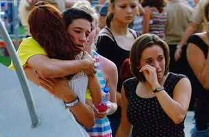 Friends and family members of the 12 Batman movie shooting victims hug during a memorial vigil in Colorado.