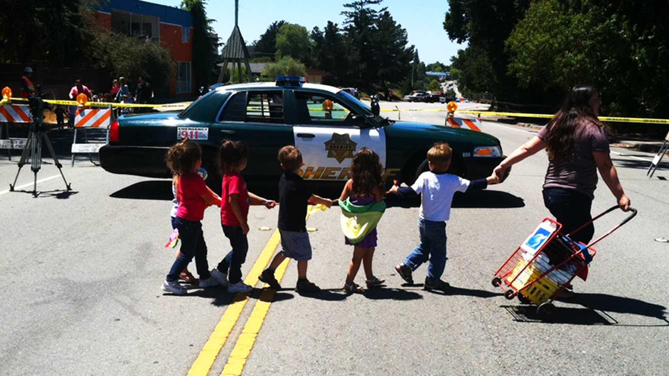Preschool students are curious as they are escorted away from their school because of a gas leak. (Aug. 7, 2012)