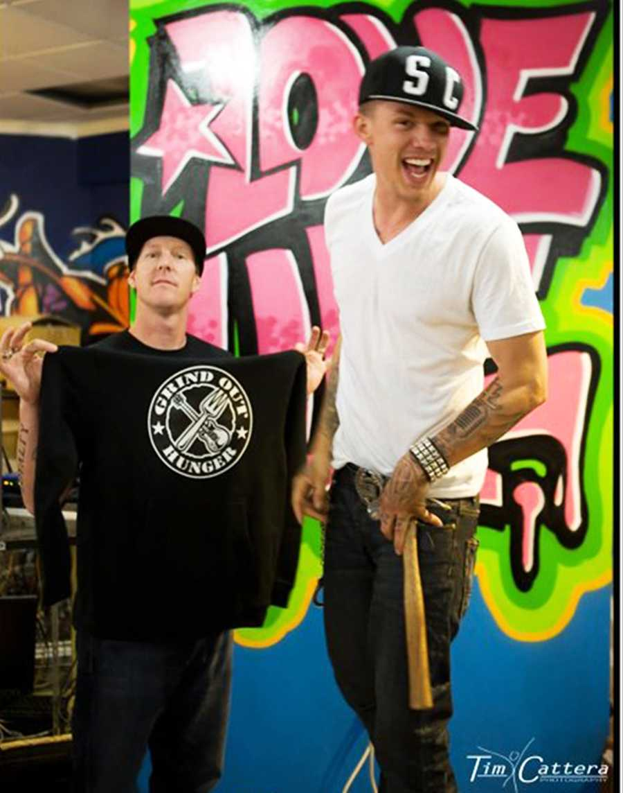 Danny Keith, left, and singer-songwriter Chris Rene are all smiles inside Grind Out Hunger's new headquarters. (Sept. 1, 2012)
