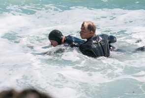 The injured surfer, left, is seen here as Craft, right, made sure his head stayed above water.The surfboard's leash had wrapped around the 50-year-old man's severely leg broken leg, making it even harder for him to stay above the ocean's surface.