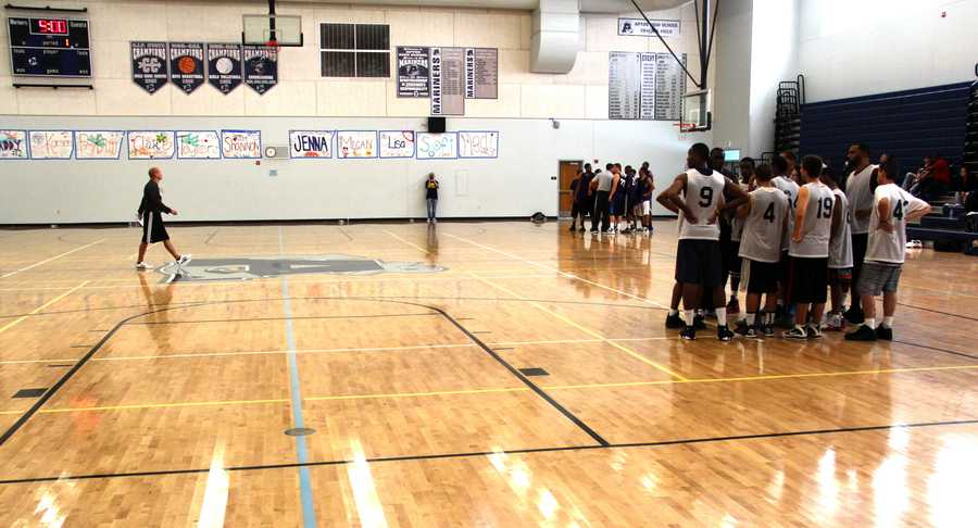 Basketball players trying out for the team huddle up. Santa Cruz Warriors Head CoachNate Bjorkgrenis seen on the left.