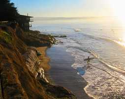 """A surfer enters the ocean to surf at a wave break called """"Jack's,"""" which is directly below Jack O'Neill's Santa Cruz house."""