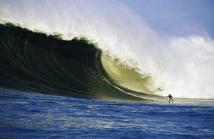 Flea is surfs a monster Mavericks wave in Half Moon Bay. / Frank Quirarte Photography