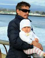 Darryl Virostko holds his daughter while watching waves on Santa Cruz' westside. / Photo by Erik Colasanti