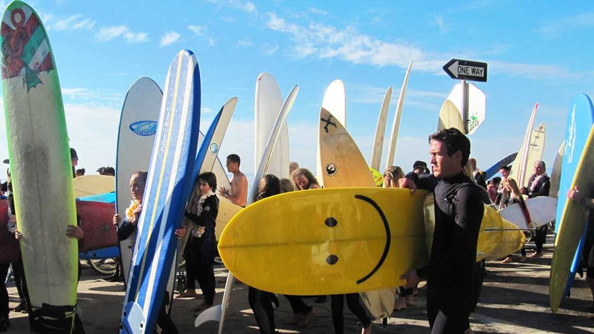 A surfer carries a smiley face surfboard in Santa Cruz.