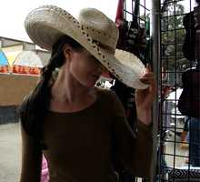 KSBW Digital Media Manager Amy Larson tries on some western-style hats at the rodeo.