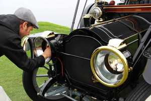 Derek Hill, a concours judge and owner of this 1912 Packard, ignites a flame inside the Packard's headlights.