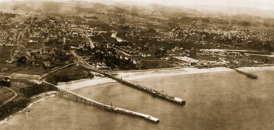 This aerial photo taken in 1906 shows Cowell Wharf (left), Railroad Wharf (middle), and Pleasure Pier (right).Photo by George R. Lawrence from the Library of Congress collection.