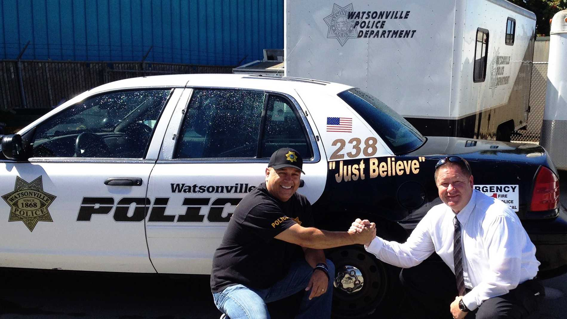 "Watsonville Police Chief Manny Solano shakes hands with police Lt. Terry Traub. Patrol cars were marked with ""Just Believe"" while the chief underwent treatment for cancer."