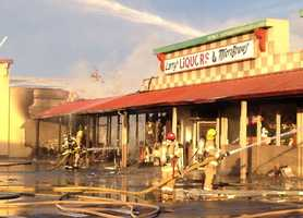 A fire at a shopping complex in Hollister tore through two stores, burning them to the ground, and damaged two neighboring businesses Sunday.