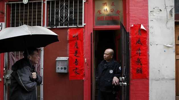 An SFPD officer is seen in the doorway of the Ghee Kung Tong Chinese Free Masons Temple in San Francisco's Chinatown on Mar. 26, 2014.