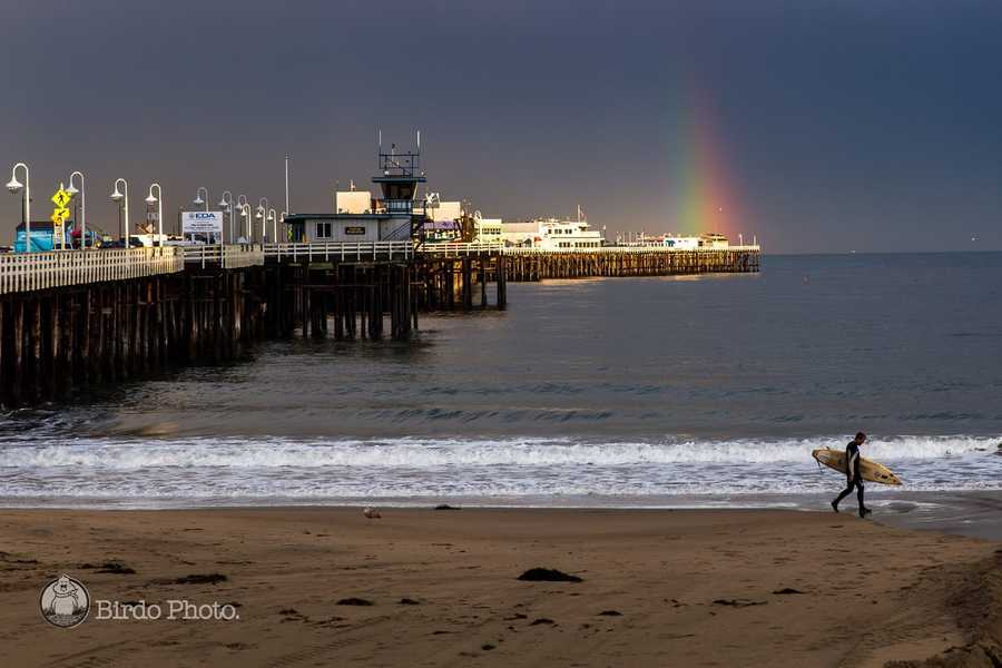 A surfer walks past the Santa Cruz Wharf as a rainbow glimmers over the ocean on March 31, 2014. See more photos by Birdo here.