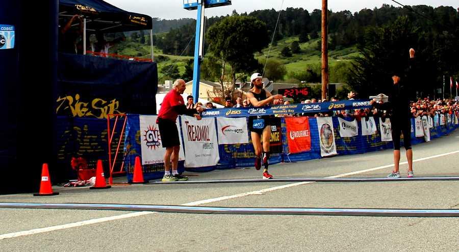 Michael Wardian crosses the finish line to win the 2014 Big Sur International Marathon.