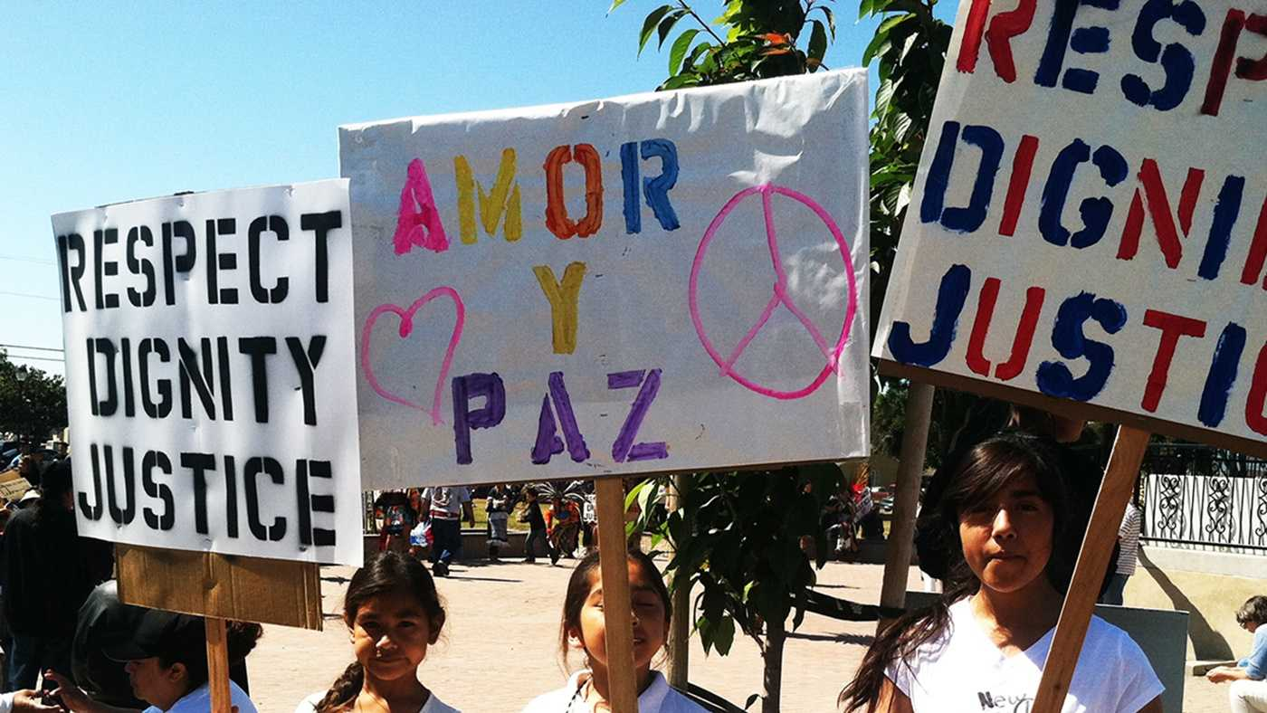 Girl hold signs calling for respect, dignity, justice, love, and peace during a march in East Salinas. (May 25, 2014)