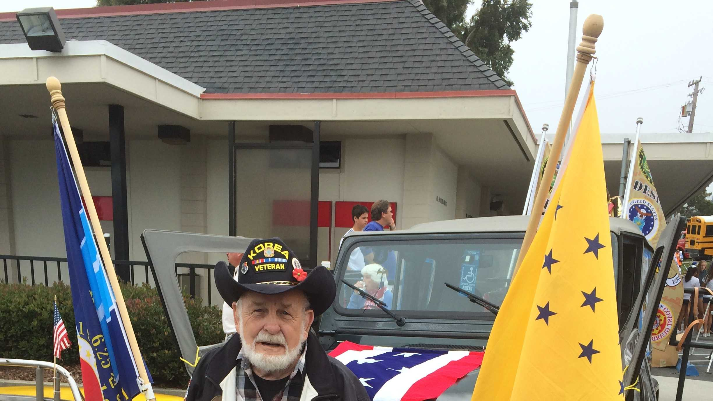 Korean War veteran Jim Brush poses with his jeep before Friday's World's Shortest Parade in Aptos