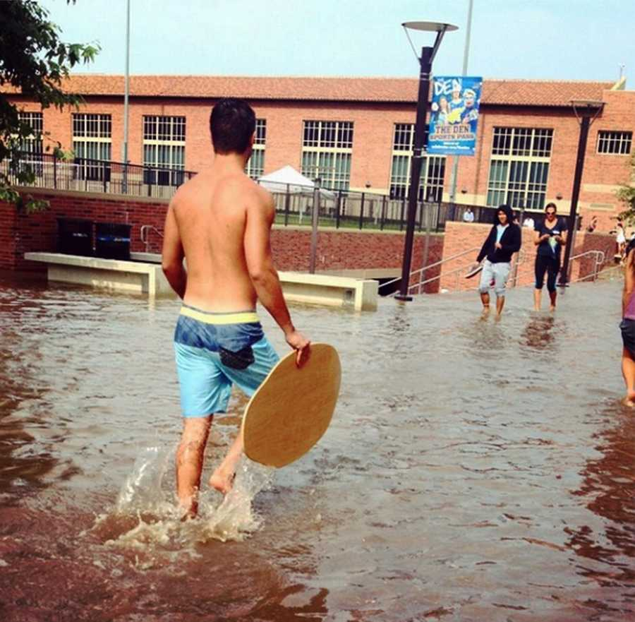As their campus was covered in 8 million gallons of water Tuesday, barefoot students pulled out their skim boards and boogie boards for a chance of fun.