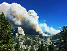 Fire officials called in additional crews to help battle a blaze in Yosemite National Park that has so far forced hikers to be airlifted off Half Dome's peak and sent smoke into the park's famed valley for the first time Tuesday.