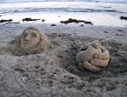 """Professional sand artists with Santa Cruz Sand made this Monday in support of Grey Bears.""""Grey Bears is run by senior citizens and distributes food to those in need, hence the hand giving (or receiving) the apple,"""" Santa Cruz Sand said."""