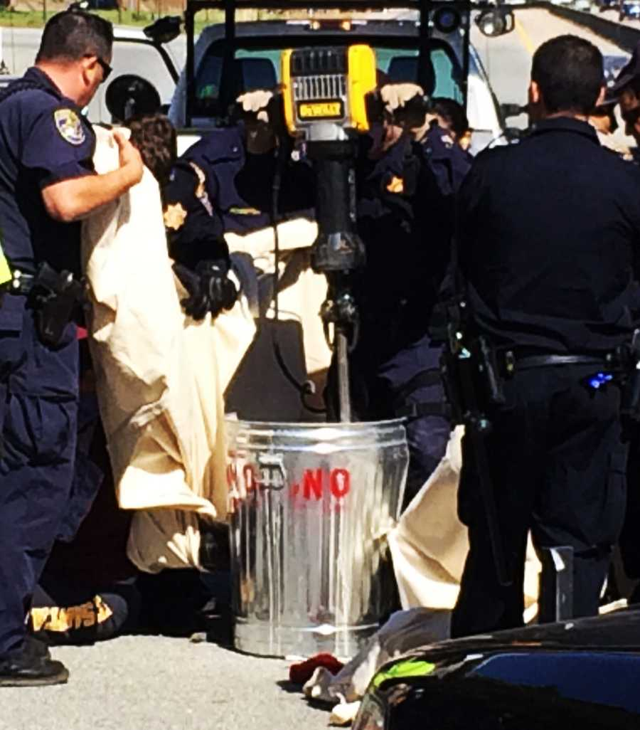 Crews used a jackhammer to detach the students from the cement-filled trash cans. Officers put safety goggles and other protective gear on the protesters.
