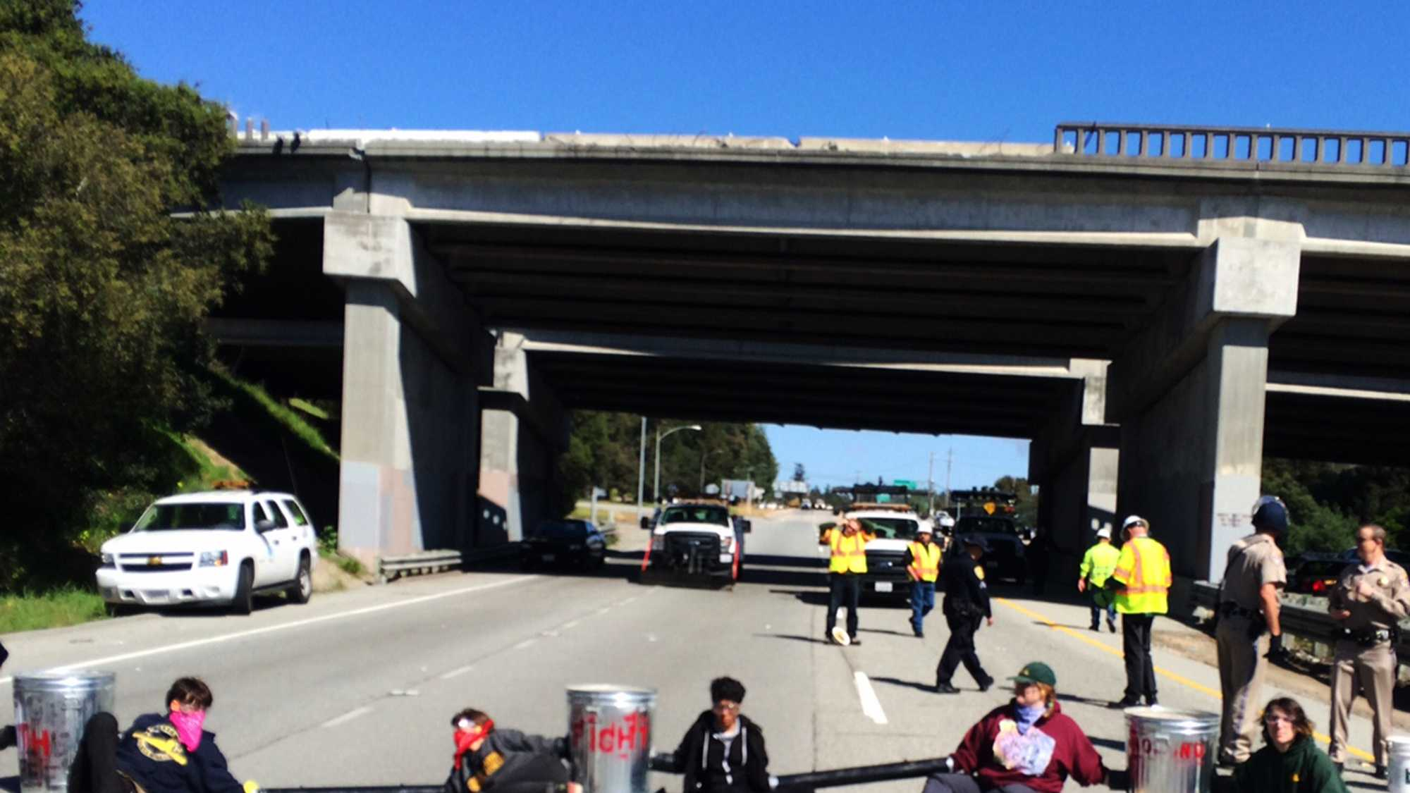 A human blockade with cement-filled trash cans was created on Highway 1 in Santa Cruz. (March 3, 2015)