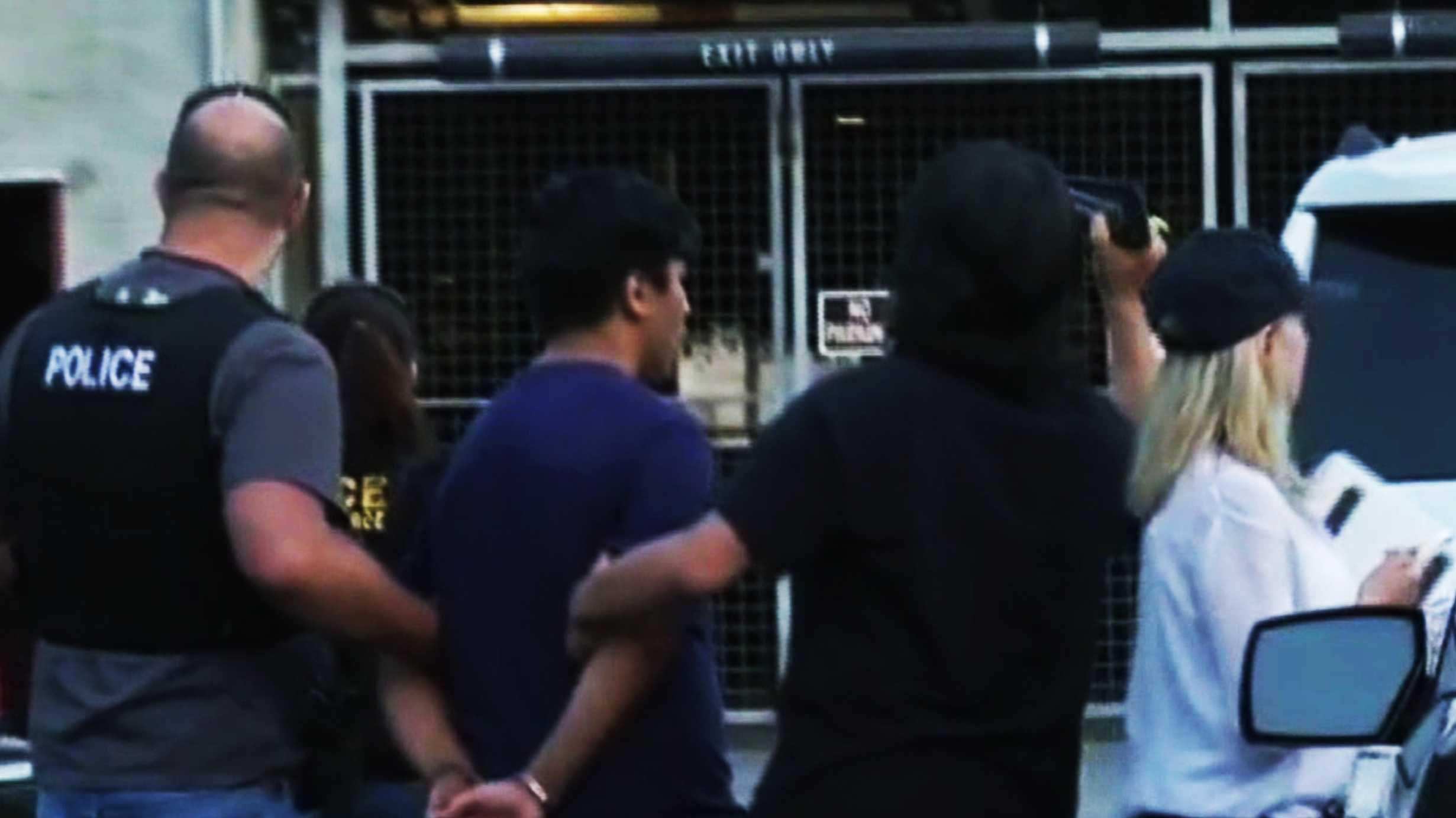 A 15-year-old Santa Cruz boy is led away in handcuffs on July 27, 2015.