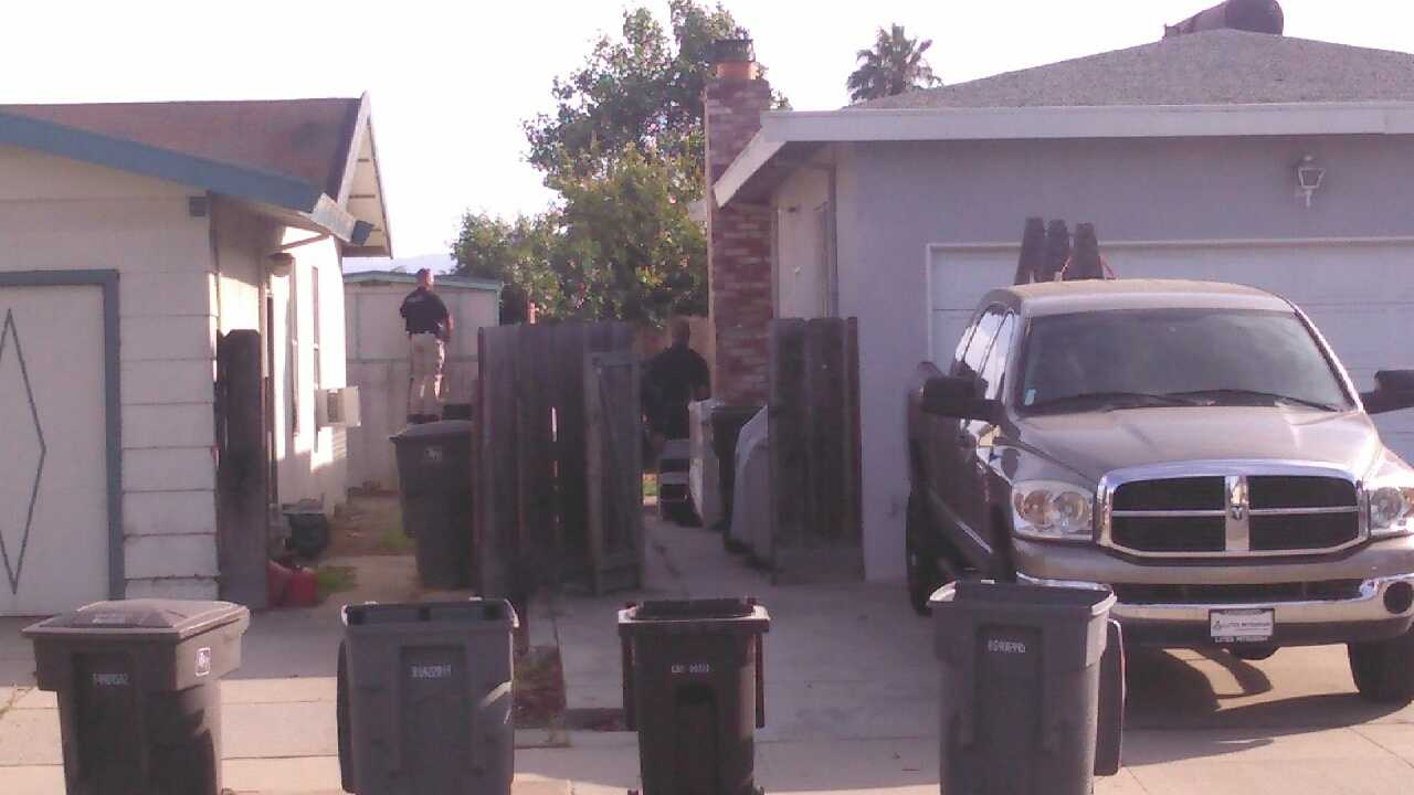 Salinas police surround a home where they believe murder suspect Brad Azcona is hiding
