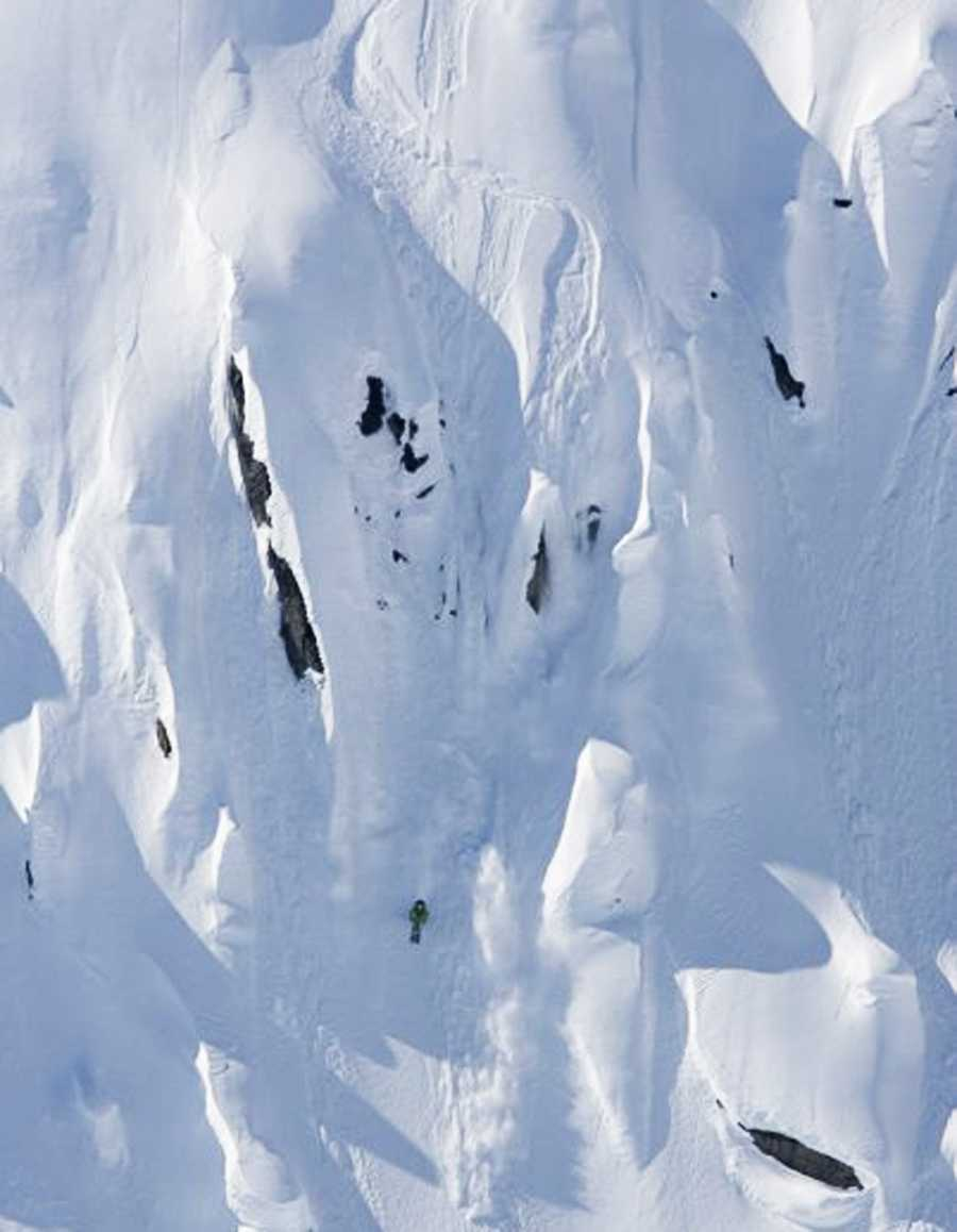 Elyse Saugstad is seen skiing a vertical snowy cliff. She is an Alpine ski racer and free rider.