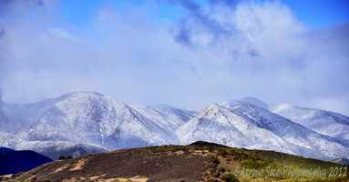 Snow coated mountains are seen from Carmel Valley Road in the Arroyo Seco area of southern Monterey County.  (March 19, 2012)