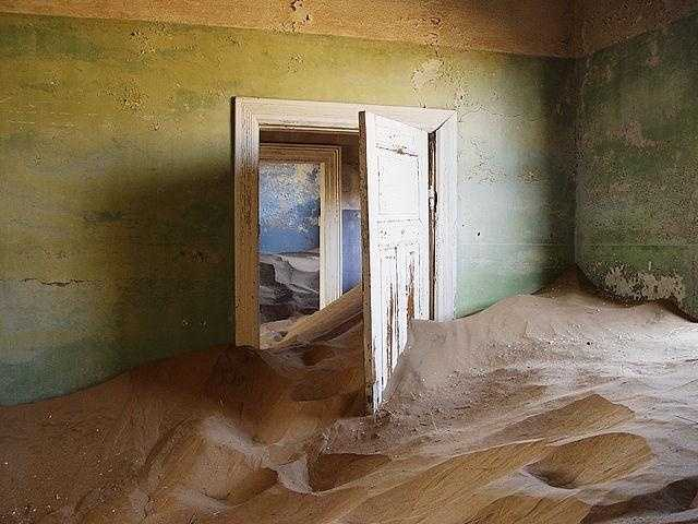 A couple of buildings are still standing, but the rest are crumbling ruins buried in sand.