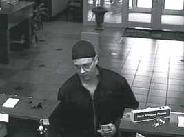 A man in his late 20s to early 30s robbed two bank tellers at gunpoint and got away with an undetermined amount of cash, police said.