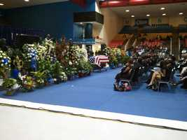 The family of slain Detective Eric Smith sit before his flag-draped casket during a funeral at JSU's basketball arena.