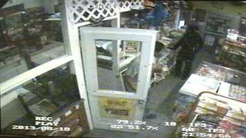 Another clerk walks into the store and gains the robber's attention.