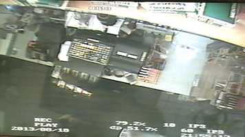 The robber can be seen taking cash from the drawer.