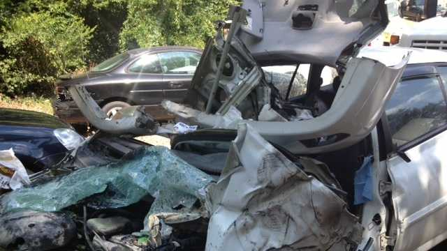 What remains of a car that collided with a school bus.