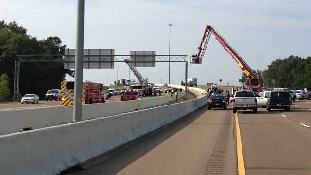 A ladder truck brings a man down from a highway sign.