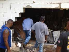 Two women inside the house were hurt when the car barreled through the house, witnesses said.