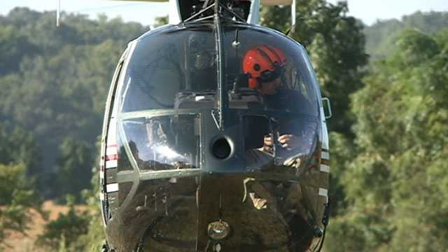 A helicopter is used to fly the linemen to the power poles.
