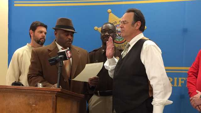 Actor and comedian Dan Aykroyd is sworn in as an honorary deputy by Hinds County Sheriff Tyrone Lewis.