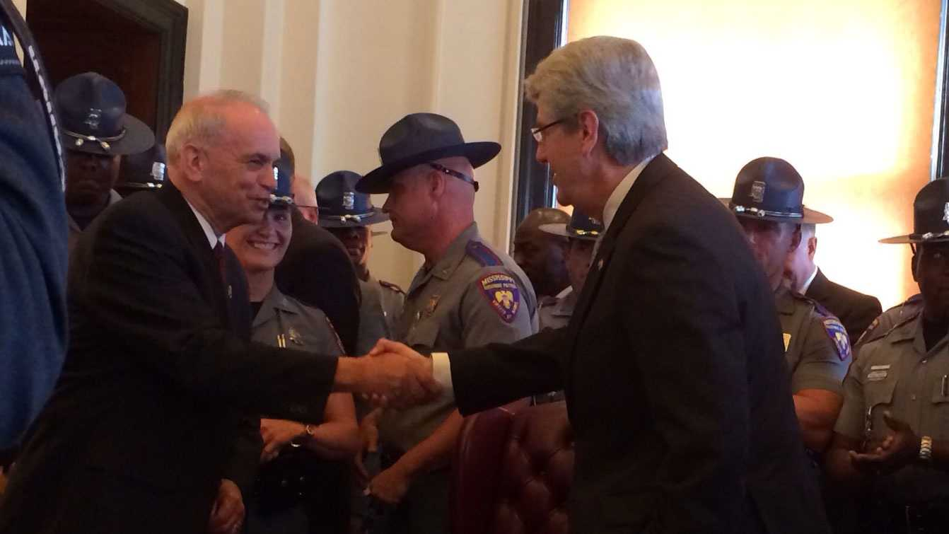 Gov. Phil Bryant shakes hands with DPS Commissioner Albert Santa Cruz after signing bill to fund MHP trooper training.