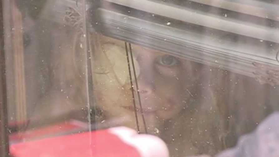 Victoria Wilcher peeks through the window of her family's Simpson County home.