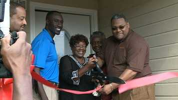 Jackson Police Chief Lee Vance, Mayor Tony Yarber and MAC Construction president Marcus Wallace help Johnnie Johnson cut the ribbon to her new house.