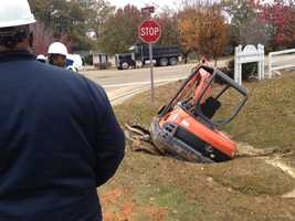 A backhoe falls into a hole as a city water crew works to repair a water line on Siwell Road.